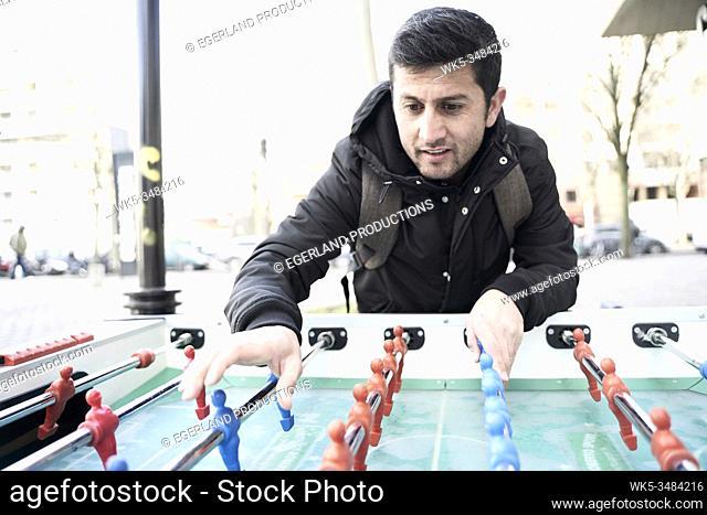 Afghan man playing foosball, table soccer