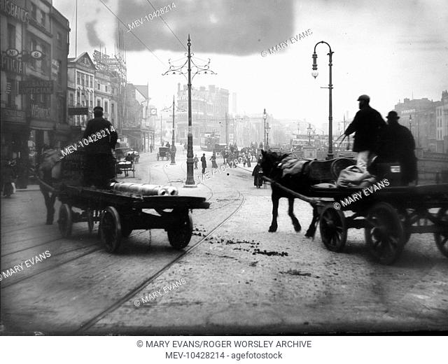 A street scene near Bristol harbour, Bristol, with horses and carts in the foreground. Tramlines can be seen in the roadway