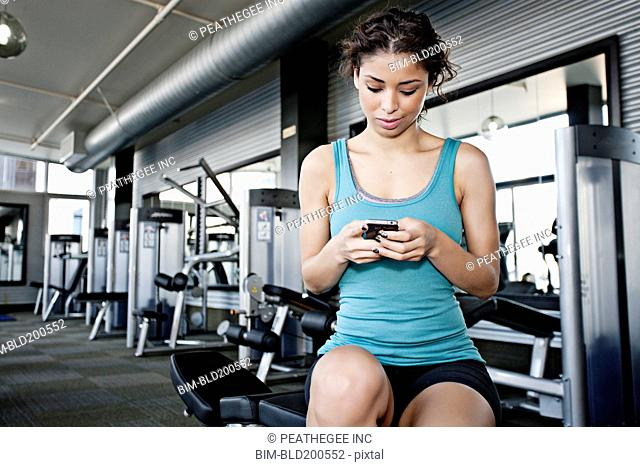 Mixed race woman text messaging on cell phone in health club