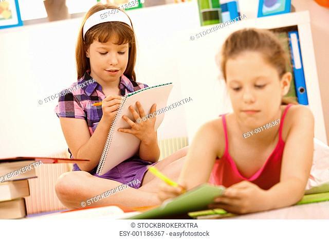 Schoolchildren writing into booklet