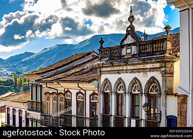 Facade of old houses built in colonial architecture with their balconies, roofs and colorful details with the mountains in the background in the historical city...