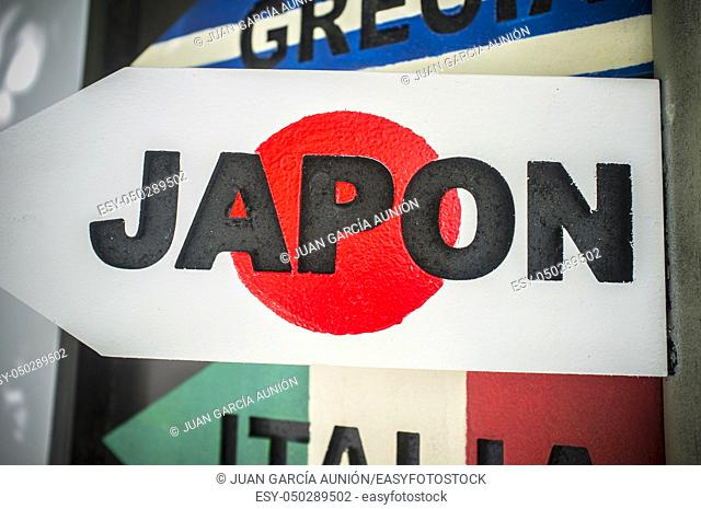 Pole guidepost with Japan sign and flag as background. Travel concept