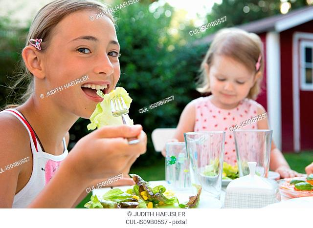 Portrait of girl eating salad in garden, Bavaria, Germany