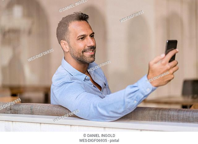 Smiling businessman with cell phone behind windowpane