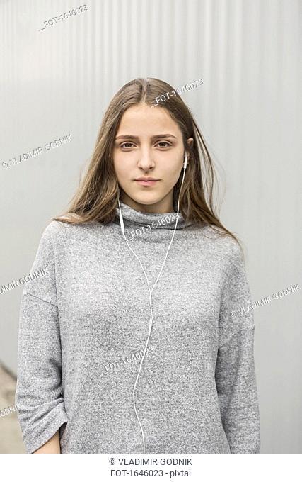 Portrait of teenage girl listening to music in headphones against wall