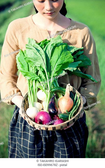 Young woman in field holding basket of homegrown vegetables