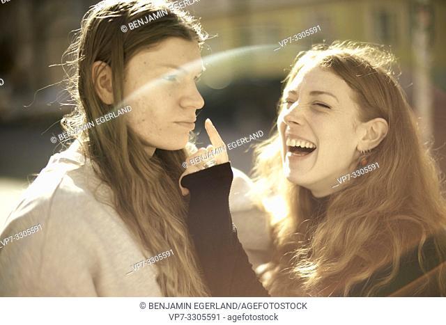 couple outdoors in sunlight, joking woman touching nose of man, making fun, in Berlin, Germany
