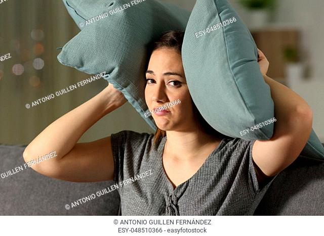 Desperate woman covering ears to protect from neighbour noise sitting on a couch in the living room at home