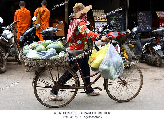 Woman pushing her bike selling fruit in the streets of Phnom Penh,Cambodia,South Esat Asia