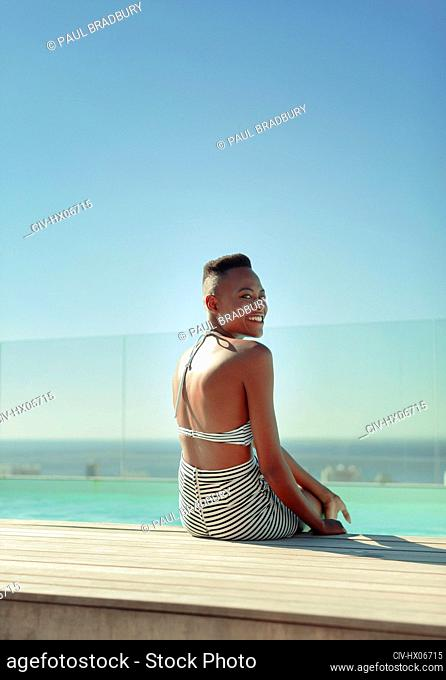 Portrait smiling, carefree young woman at sunny poolside