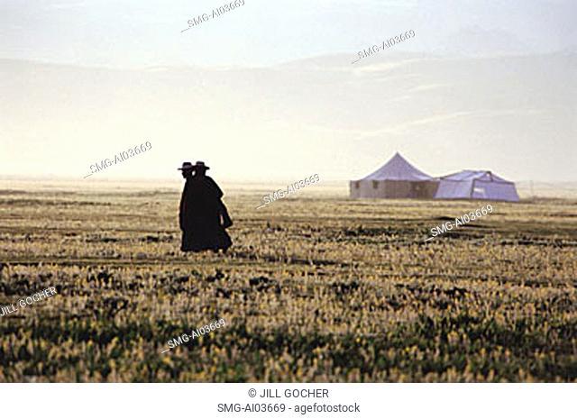 China, Szechuan (Sichuan), Kham region, Tibetan monks walk along grasslands in early morning, tents from a Kham festival in background