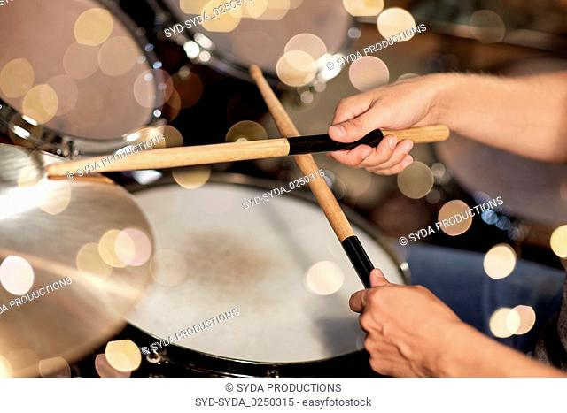 male musician hands with drumsticks at concert