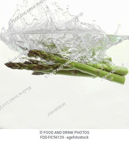 Asparagus splashing into water