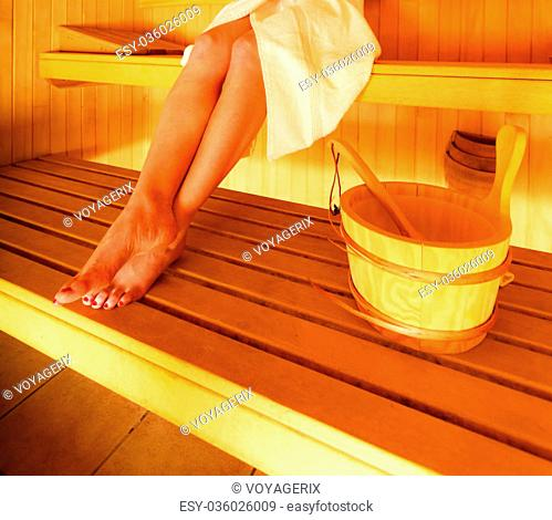 Spa beauty well being and relax concept. Woman white towel sitting relaxed in wooden sauna, part of body legs