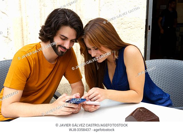 Young couple looking at the mobile on a summer terrace, smile while they wait