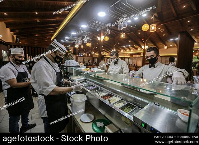04 June 2020, Palestinian Territories, Gaza City: Chefs and waiters are seen wearing face masks as they prepare plates for c
