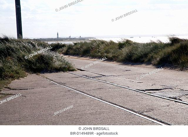 Road next to eroded railway line at Spurn Head, East Yorkshire, England