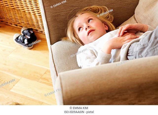 Young girl lying in armchair, looking away