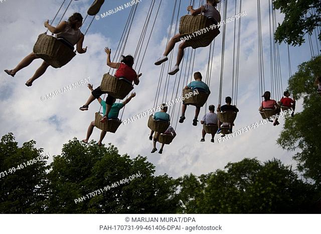 Visitors take a ride on a chairoplane at the adventure park Tripsdrill in Cleebronn, Germany, 31 July 2017. Photo: Marijan Murat/dpa