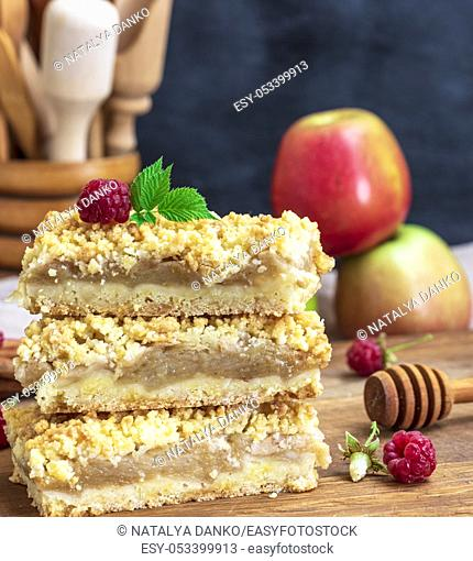stack of square baked pieces of cake with apples on a wooden board, crumble cake