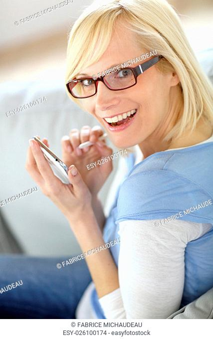 Cheerful girl using smartphone sitting in sofa