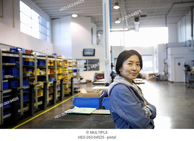 Portrait confident worker with arms crossed in factory