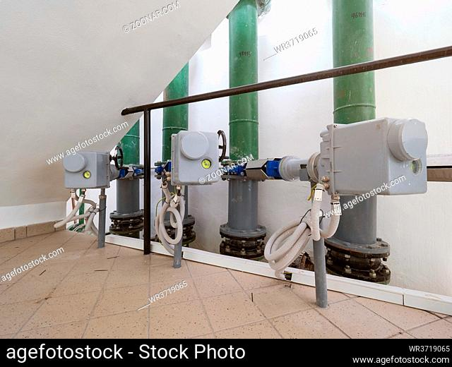 Modern pumping station with vertical piping and motors with servo drive on valves controlled remotely from the control room