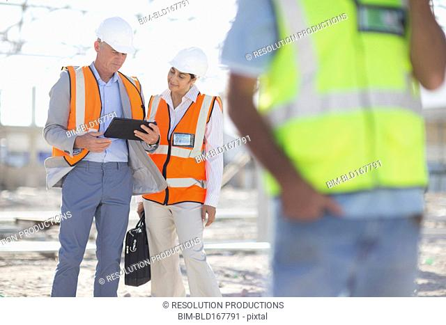 Architects using digital tablet at construction site