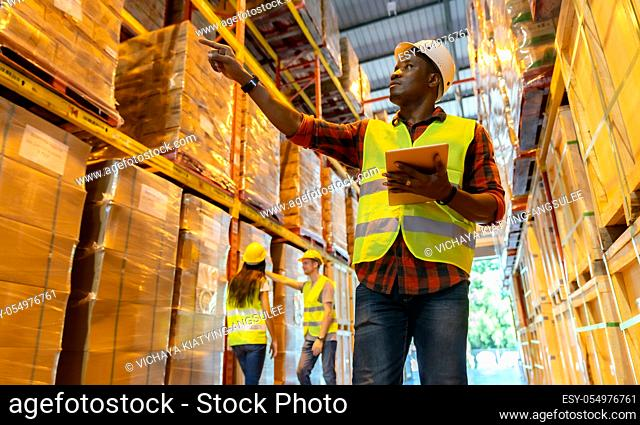 Portrait african black warehouse supervisor standing with digital tablet check stock in large warehouse distribution center with colleague worker in background