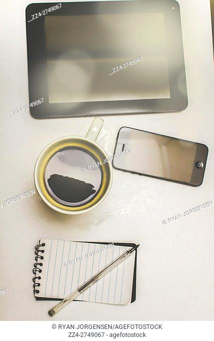 Composition of smartphone, tablet, coffee and notebook with pen on white table. Contemporary business desk