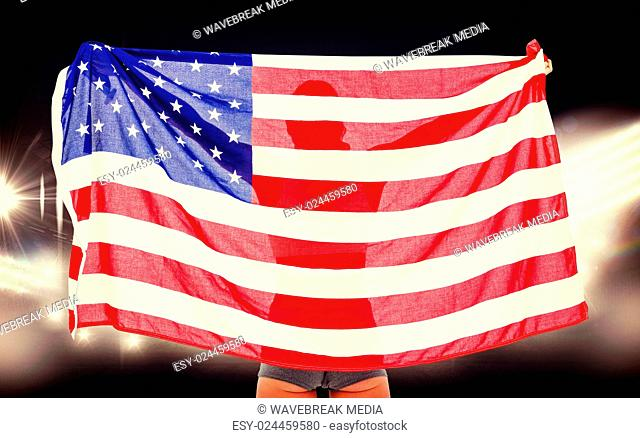 Composite image of athlete posing with american flag after victory
