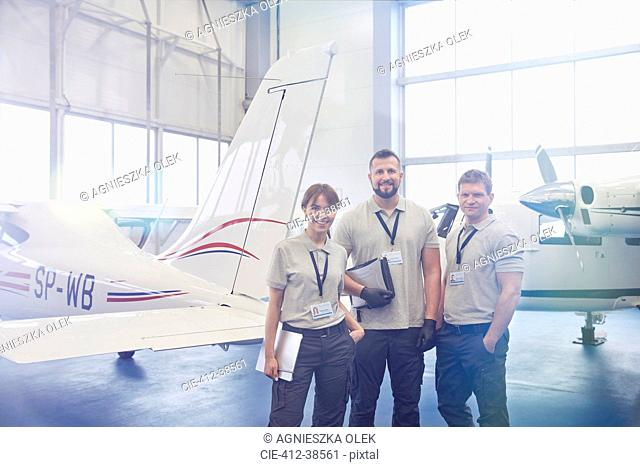Portrait confident mechanic engineers standing in airplane hangar