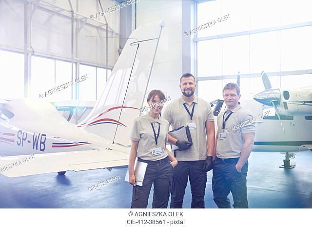 Portrait confident mechanic engineers standing in airplane hangar