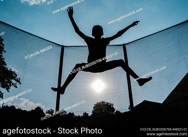 Horizontal front backlighting photo of a silhouette of a barefoot young boy jumping or flying on a trampoline with net and the sun at the background reflecting...