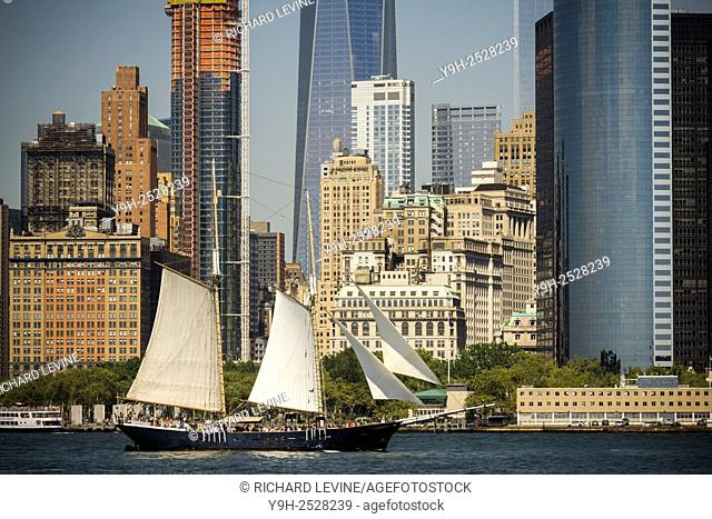 A sailboat on a tour floats past the Lower Manhattan skyline seen from Governor's Island in the New York Harbor