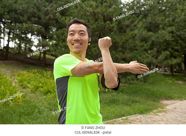 Young male runner stretching arms in park