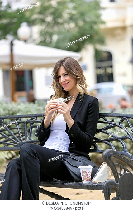 Executive woman ejoying her break with sandwich and coffee in the park