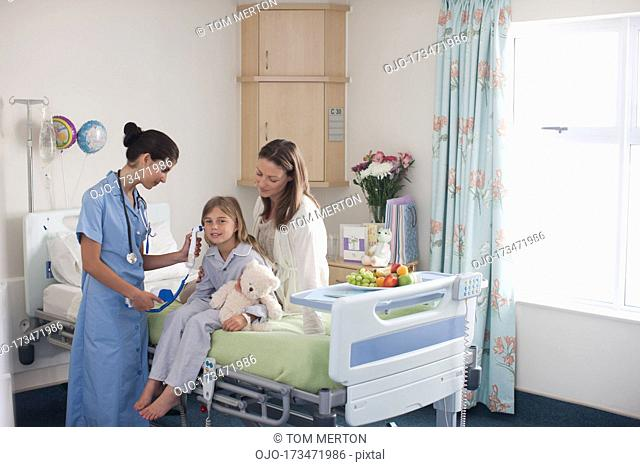 Nurse in children's hospital with girl patient and mother