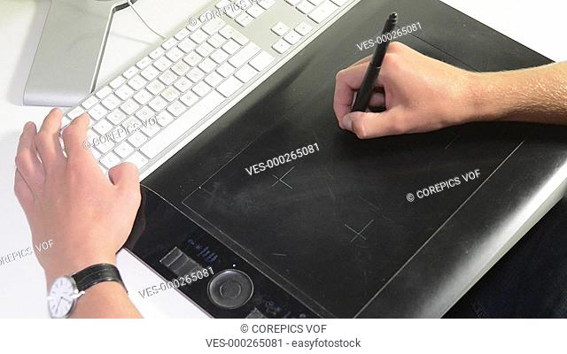 Product engineer at work creating conceptual sketches using a tablet and a computer. Zooming out to show part of the screen