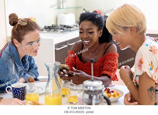 Young women friends enjoying breakfast, using smart phone in kitchen