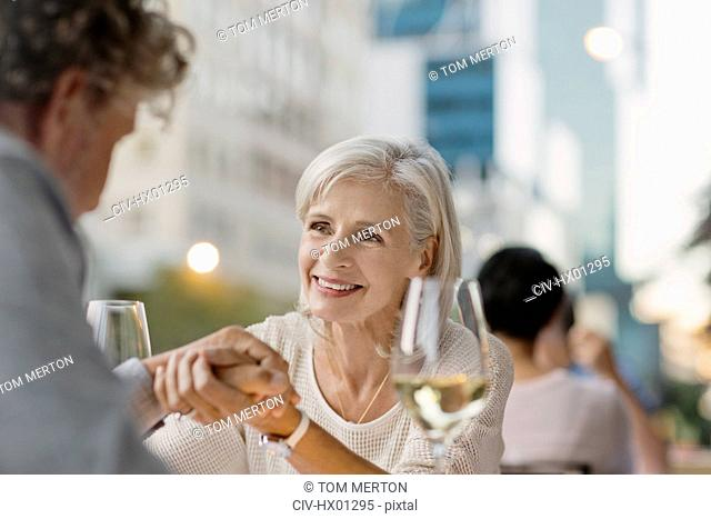 Affectionate senior couple holding hands drinking white wine at urban sidewalk cafe