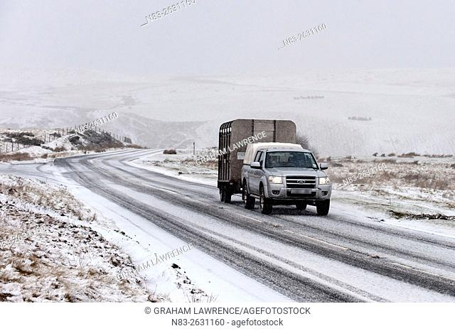 A 4WD vehicle and trailer negotiates the B4520 high moorland road between Brecon & Builth Wells in a wintry landscape, Powys, Wales, UK