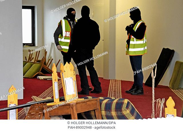 Masked German police officials inside the rooms of the German-speaking Islamic Society of Hildesheim (DIK) mosque in Hildersheim, Germany, 14 March 2017