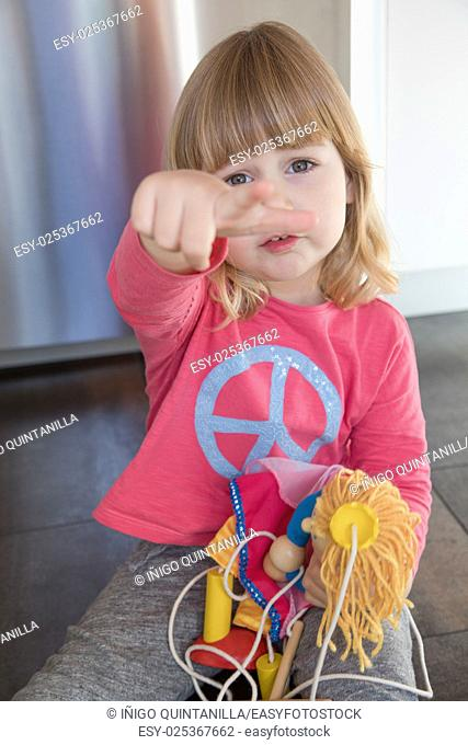 portrait of blonde three years old child with pink shirt blue peace hippie symbol, sitting on floor kitchen, annoying expression