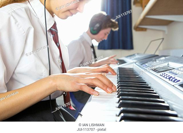 Close up high school student playing piano in music class