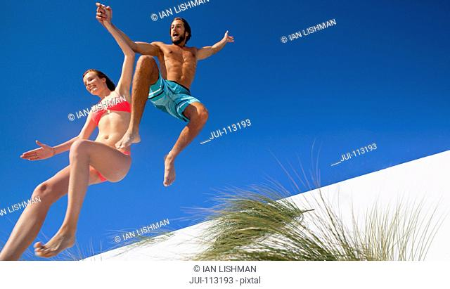 Exuberant couple jumping over sand dune beach hill