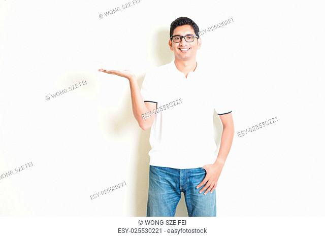 Dining concept. Indian waiter holding an empty plate on hand, ready for food. Asian man standing on plain background with shadow and copy space
