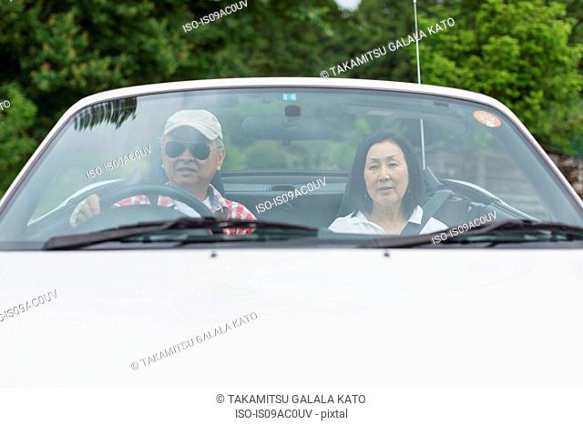 Couple enjoying leisurely drive in sports car
