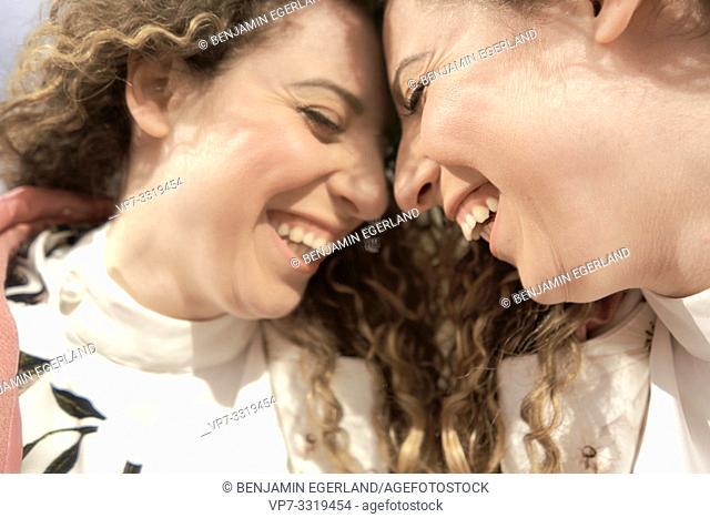laughing woman facing herself