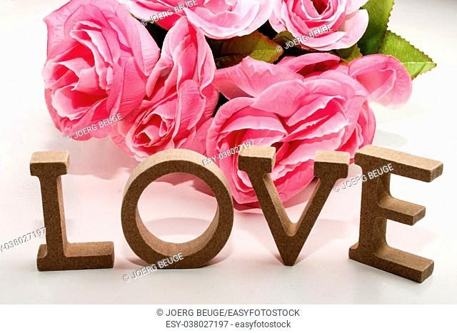 bouquet of pink flowers on a white background and the word love made with wooden letter